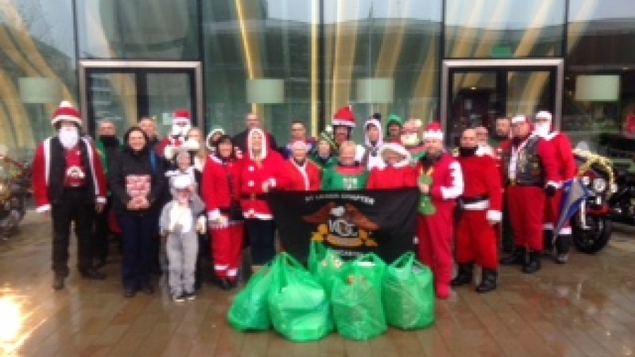 Members of the St Leger Harley Davidson Club hand over sacks full of toys.