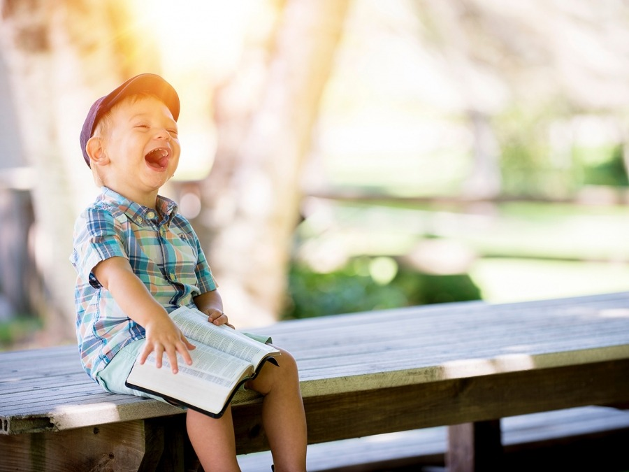 Child laughing sitting on table