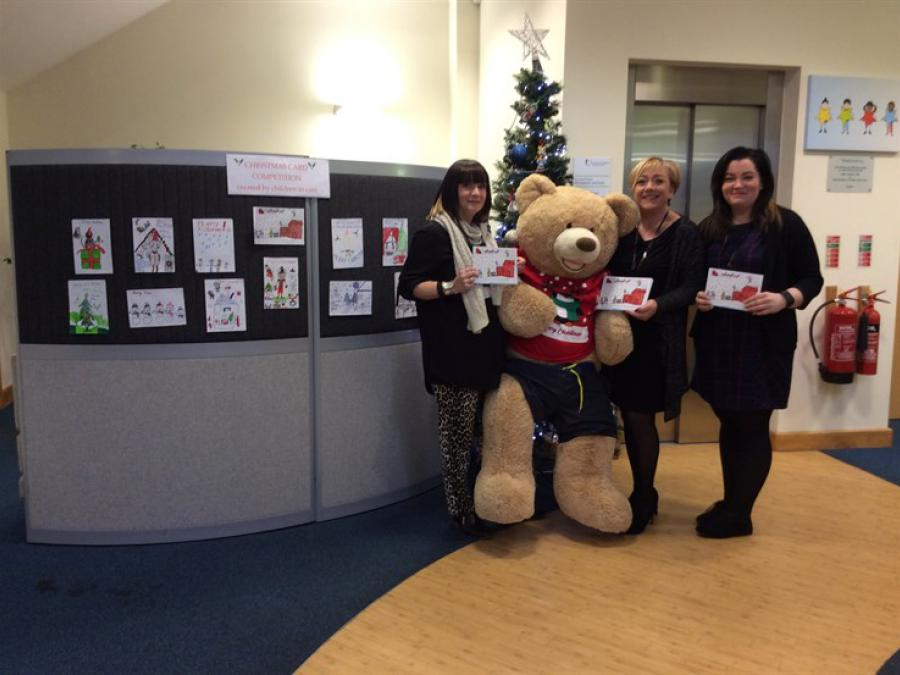 Advanced Practitioner Sam North, Social Work Assistant Tracey Baker and Business Support Officer Michelle Craven, with the Christmas card entries and the winning design, which has been turned into the official Doncaster Children's Services Trust festive c