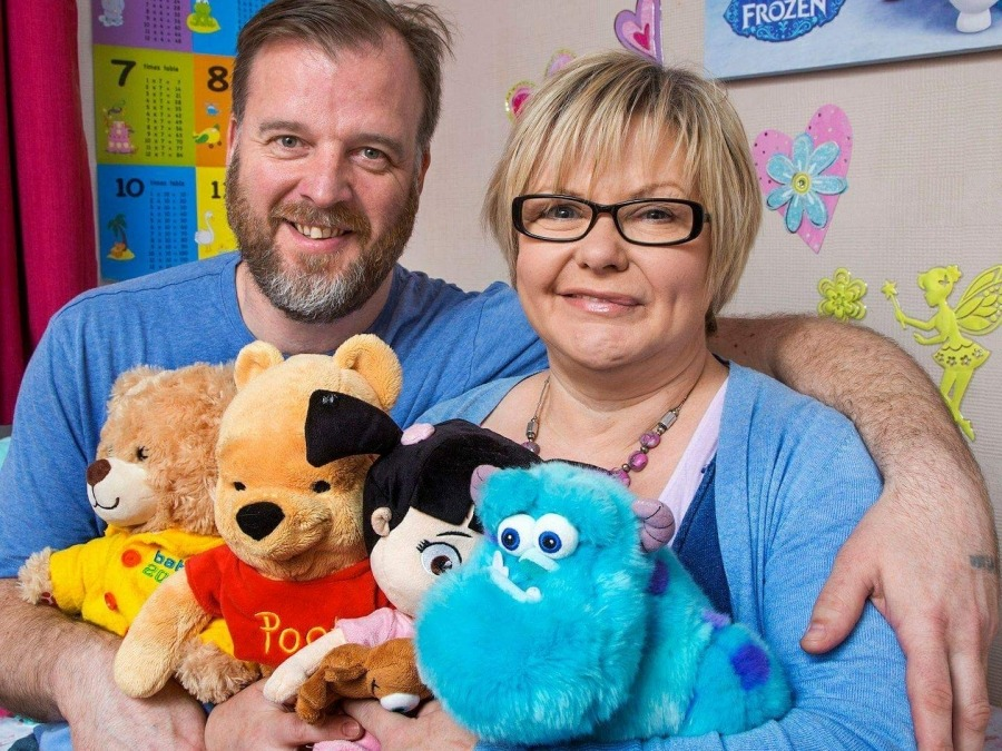 Foster carers holding children's toys