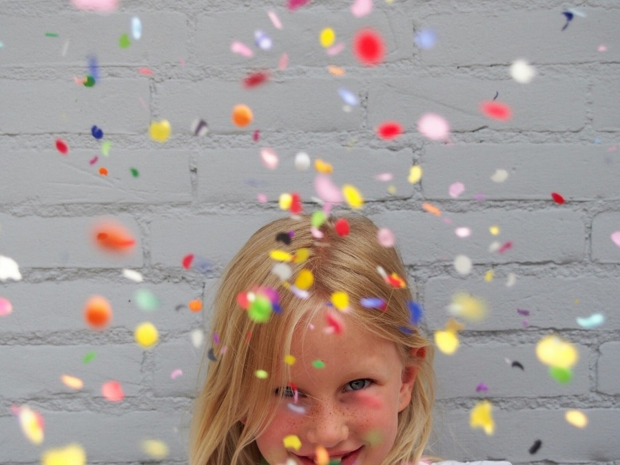 Little girl throwing bright coloured confetti